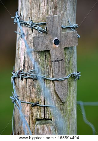 Wooden cross on a post wrapped in barbed wire