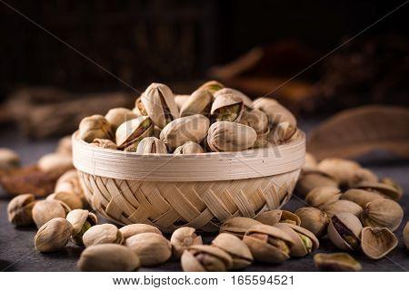 not peeled pistachios in a wicker basket.