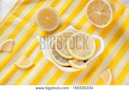 Sliced lemon on a plate shaped striped yellow background