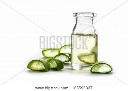 Slices of fresh aloe vera leaf and a bottle with the transparent gel used for medicinal purposes skin treatment and cosmetics isolated with shadow on a white background cose up shot with selective focus and narrow depth of field