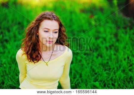 Beautiful portrait of dreamy pretty woman meditating in the Park on blurred background of green grass closeup.