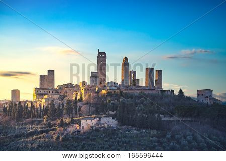 San Gimignano town skyline and medieval towers sunset in blue hour. Italian olive trees in foreground. Tuscany Italy Europe.