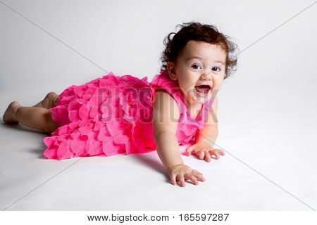 A happy Native American Hispanic baby lays on her tummy in a frilly pink dress on a white background. She reaches toward the camera with her right arm.