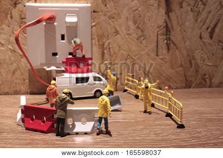 Small Workers Work At Electric Plug