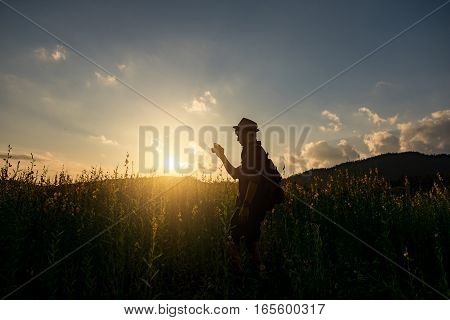 Silhouette of a young who like to travel and photographer taking pictures of the beautiful moments during the sunset sunrise
