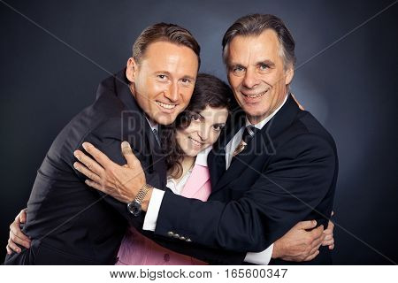 studio shot of a hugging business team after just shaking hands for so many years, they felt like they were ready for the next step in their business relationship