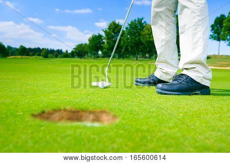 golf player getting ready to put, having a huge hole he cannot possibly miss