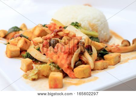 Stir Fried Tofu With Gravy Sauce And Mixed Vegetables In White Plate On White Background. Vegetarian