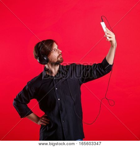 Man listening to your favorite music on headphones. He does selfie phone. Hipster in a black shirt on a red background.