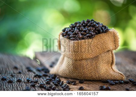 coffee beans in a sack bag on wood table