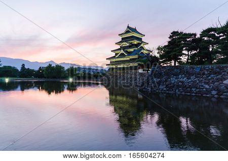 Matsumoto castle and sunset sky reflect on water at nagano japan