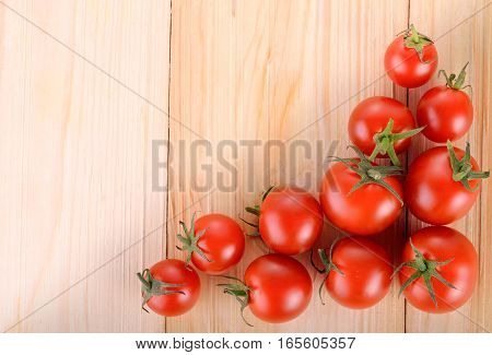 red tomato with stem on wooden table background with left space for writing or text