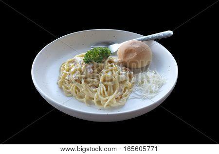 Spaghetti Carbonara with bun on black background