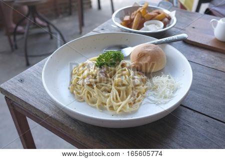 Spaghetti Carbonara with bun and French fries on wood table