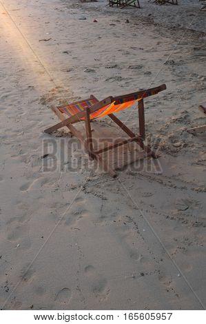 Deckchair on the sand beach during sunset