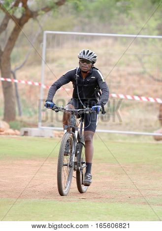 Middle Aged Black African Man Riding To The Finish Line At Mountain Bike Race