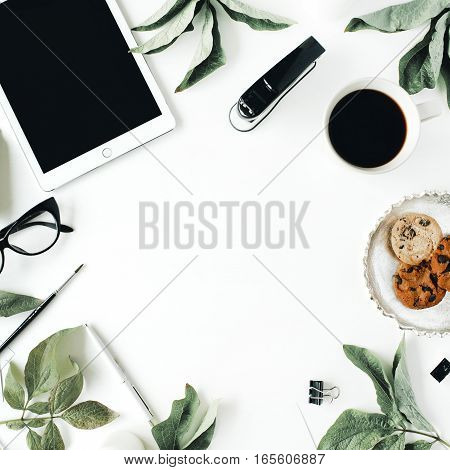 Workspace with tablet glasses cup of black coffee cookies on golden tray paintbrushes and leaf. Flat lay composition for blog. Top view.