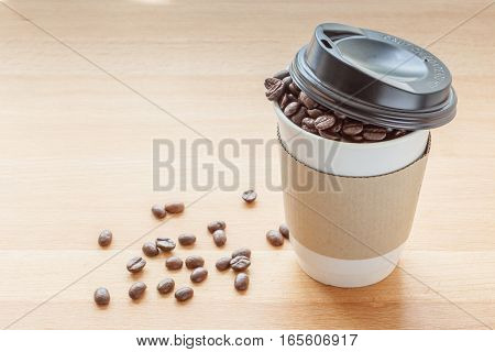 A paper cup of full roasted aroma coffee beans and some fallen on wooden board background.