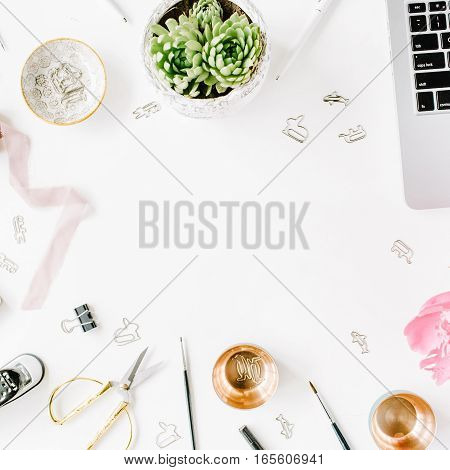 Workplace with laptop succulent peonies golden scissors spool with beige ribbon pencils and diary. Flat lay composition for blog. Top view.