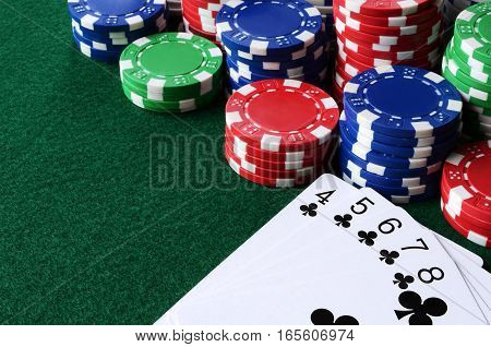 A close up image of stacked poker chips and a straight flush card hand.