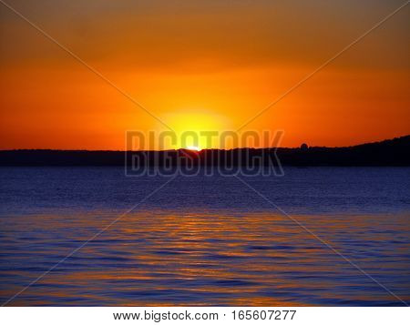 sun setting over lake Geneva and an orange sky with silhouette of the far shoreline