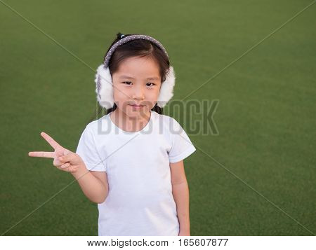 Adorable Asian Kid Girl With  Earmuffs , Green Background