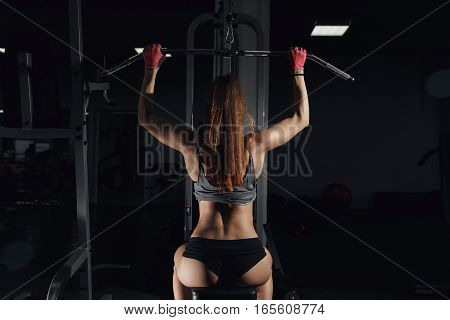 Woman Doing Exercises On A Lat Machine In A Gym.
