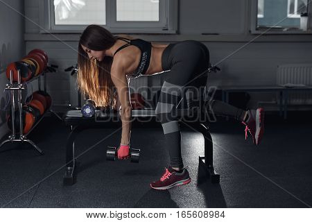 Fitness Brunette Girl With Trained Body Are Training Back With Dumbbell At Gym.