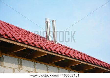 Roofing Construction Exterior. Building new house with metal red roof and steel chimney outdoor. Soffit and Fascia unfinished installation.