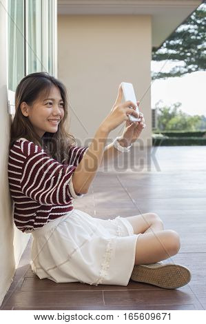 younger asian woman self portrait by smart phone