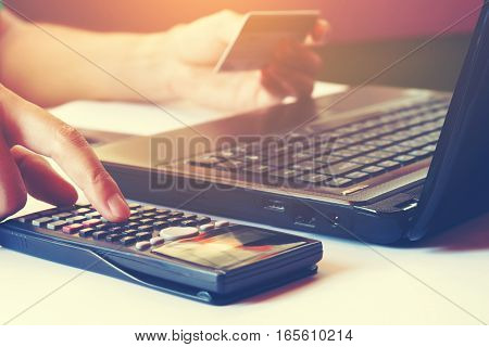 Female Calculating And Holding Credit Card With Laptop  About Cost For Shopping Online.