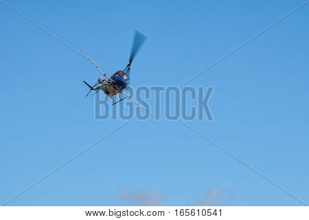 blue helicopter flies in the sky, aerial