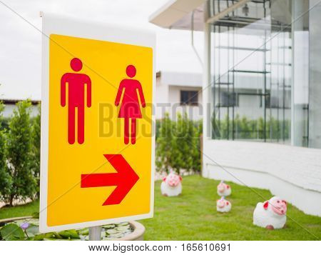 toilet sign and symbol with arrow on yellow background