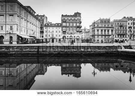 Trieste - December 2016, Italy: Facades of the old historical buildings reflected in the water canal, black and white photo
