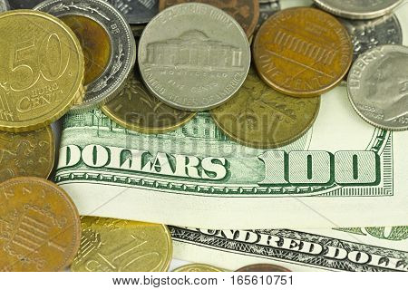 One hundred dollars with different coins close up background