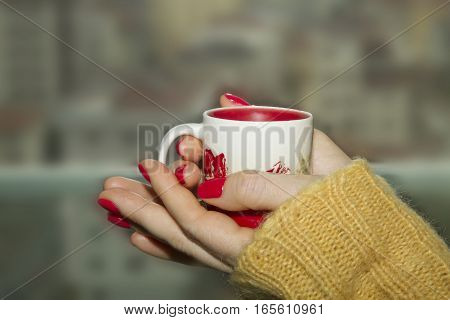 Cup of coffee or tea in womans's hands with good red manicure