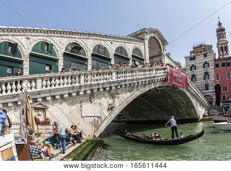 Tourists Ride On Boat Under The Rialto Bridge In Venice