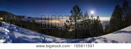 Cold Winter Snowy landscape at night with cloud inversion covering city lights that glow underneath the cloud cover. Lit with moonlight and the sky has stars.