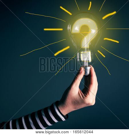 Hand with light bulb and question mark for innovation inspiration creativity brainstorming new ideas and imagination concept
