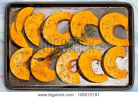 Pieces Of Pumpkin With Spices And Rosemary Branch On The Oven Tray