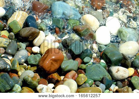 coloured sea stones on the coast in the bubble water surf background