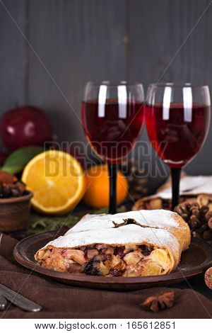 Apple strudel (pie) with dried fruits oranges cranberries walnuts with sugar and red wine on dark background. Lunch dinner for two. Romantic dinner.