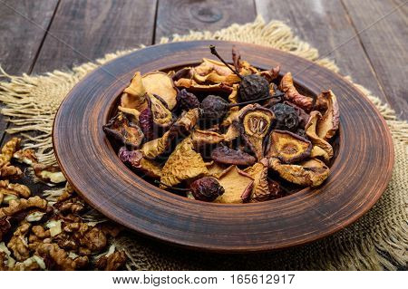 Dried fruit (apples pears apricots) berries and nuts in a bowl on dark wooden background. Close up. Ingredients for the winter vitamin drink compote.