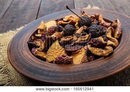 Dried fruit (apples pears apricots) berries in a bowl on dark wooden background. Close up. Ingredients for the winter vitamin drink compote.