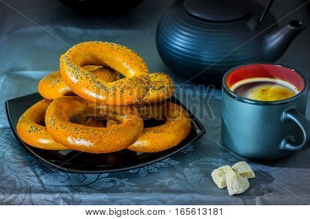 Black coffee cup with bagels on a black bowl and three pieces of sugar on a blue background