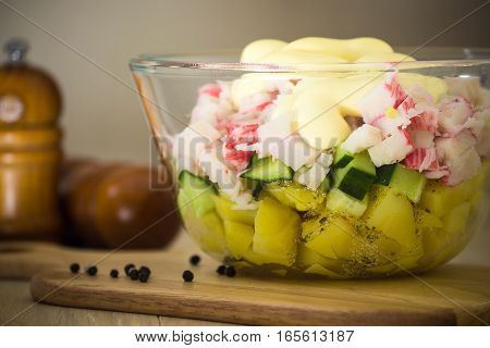 Salad from potato cucumber crab sticks mayonnaise in a transparent bowl