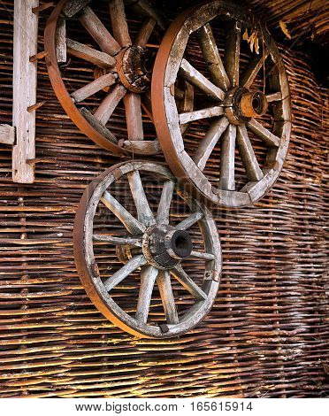 Wagon wheels hanging on a wicker fence