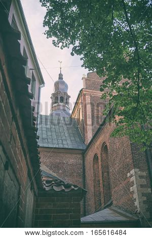 View of the steeple of the Cathedral in Riga against the backdrop of facades of old houses and green tree leaves