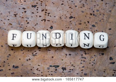 Funding Word On Wooden Cubes On A Brown Cork Background