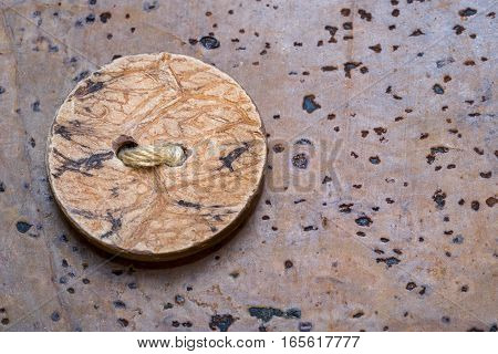 Wooden sewing button on a cork brown background